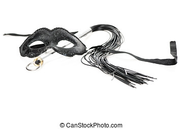 Black mask and whip on white background - A black mask and a...