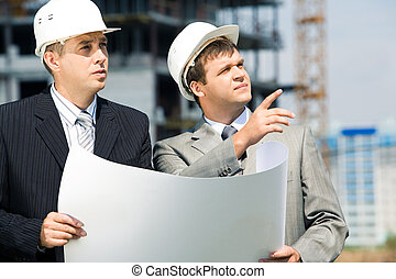 At work - Portrait of successful workers holding a project...