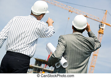 Showing - Image of two workers standing a back and showing...
