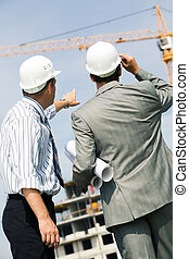 Foremen - Vertical image of foremen interacting together at...