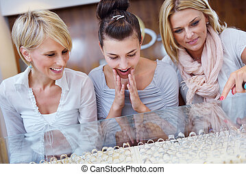 girls shopping in jewelry store - happy girls group have fun...
