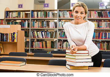 In the library - Image of teacher standing near table with...