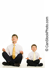 Meditating - Image of man and boy meditating in studio over...