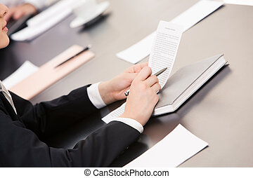 Reading a document - Close-up of businesswoman holding...