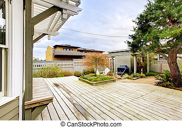 Spring backyard with large deck and wood structures.