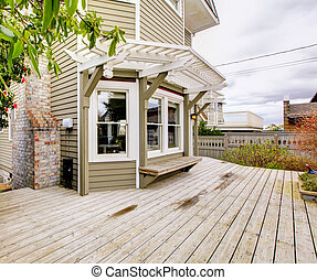 Spring backyard with house with large deck.