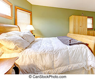 Bedroom with green walls and white bed.