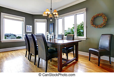 Large green dining room with leather chairs and large...