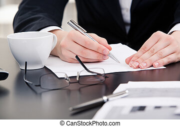 Working - Close-up of human hands holding pen over paper...