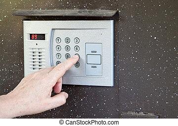 uses intercom in steel door - Close-up of uses intercom in...