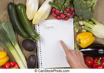 Hand pointing on book with vegetables surface