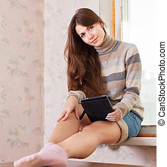 woman reads e-reader - Young woman reads e-reader at home
