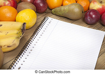 Book and fruits on wooden surface