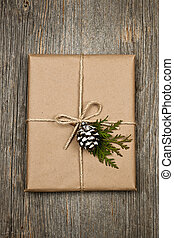 Christmas present in brown paper tied with string -...