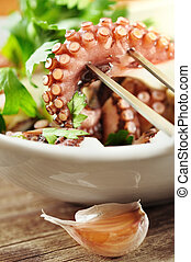 Octopus salad with olive oil, lemon and parsley, closeup