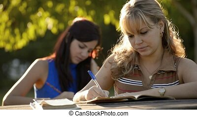 Young women studying with textbook - People and education,...