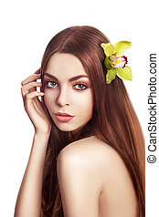 Beautiful Brunette Girl. Healthy Long Hair with Orchid Flower