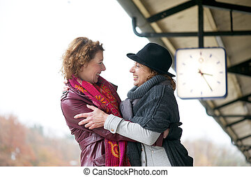 Welcoming Embrace - Two women welcoming each other with an...