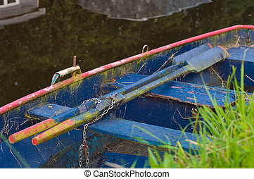 rowing boat - old rowing boat with paddles in a canal