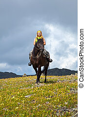 Horseback riding - Female rider on horseback at mountains