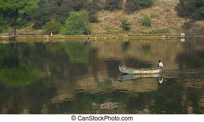Lonely boat. - A hindu rowing in a boat on the lake.