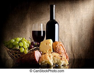 Wine bottle and food - Wine, cheese, grapes and sausage on...