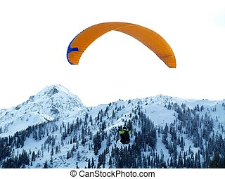 Paraglider with snowy mountain in the background.