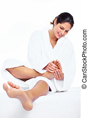Feet massage - Woman enjoying a feet massage in a spa salon...