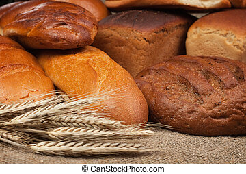 variety of fresh bread with ears of rye background