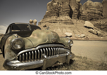 Old abandoned car at the Twin rocks in the Utah, toned image