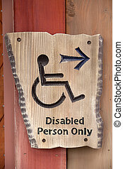 A handicapped sign on wood wall