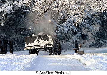 Snow cleaning tractor clears paths in a park