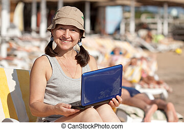 mature woman  with laptop at  beach