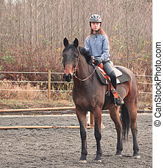 alert horse and rider - a young teenage girl with her...