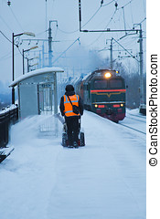 railway platform in the snow - removing snow from the...