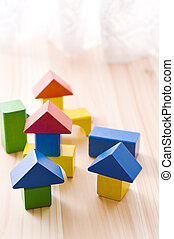 Colorful building block house on wooden floor