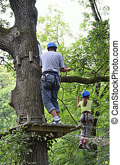 Children at ropes course on the trees - A preteen girl is...