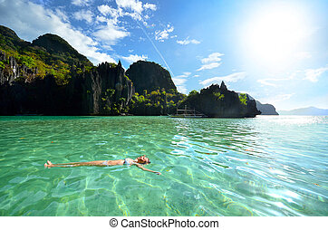 Relax on the water in the rocks - Woman resting on his back...