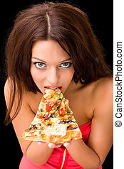 young woman eating a piece of pizza against a black...