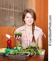 Girl with various seedlings at home - Young woman with...