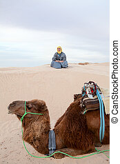 Caucasian man sitting on sand dune in desert with camel on foreground