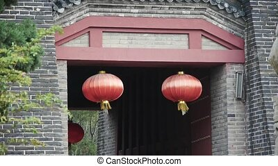 China lantern & stone lions in front of ancient city gate.