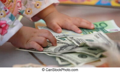 Lots of money - Child trying to gather the money from the...