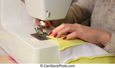 Sewing - A hand of a dressmaker supporting a cloth while...