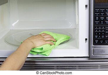 Cleaning inside of Microwave Oven - Hand with microfiber...
