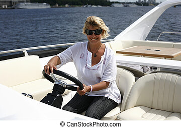 Travel - The adult woman behind a steering wheel of a yacht