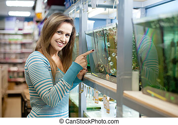 Woman in petshop - Woman near aquariums with fishes in...
