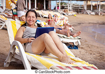 Happy mature woman  with laptop at resort