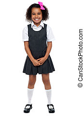 Cheerful young kid in pinafore dress posing smilingly...