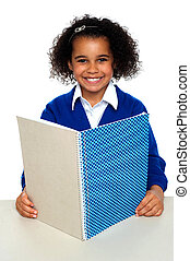 Smiling school girl learning weekly assignment. Looking...